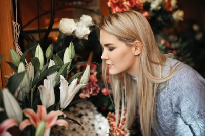woman-wearing-gray-sweater-while-smelling-the-flowers-3767383